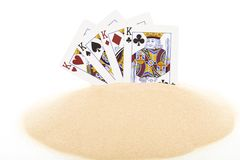 Playing cards on heap of sand. royalty free stock photos