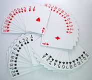 Playing cards of hearts, diamonds, clubs, spades. Playing cards from deck spread on table showing entire series of hearts, diamonds, clubs and spades Stock Photography
