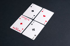 Playing Cards. High Angle View of Four Playing Cards Spread Out on Dark Background Showing Aces from Each Suit - Hearts, Clubs, Spades and Diamonds Royalty Free Stock Photo