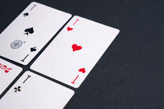 Playing Cards. High Angle View of Four Playing Cards Spread Out on Dark Background Showing Aces from Each Suit - Hearts, Clubs, Spades and Diamonds Royalty Free Stock Images