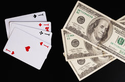 Playing cards and hundred-dollar bills on a black background. Stock Photos