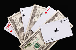 Playing cards and hundred-dollar bills on a black background. Royalty Free Stock Images