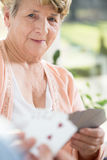 Playing cards with old woman Royalty Free Stock Images