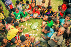 Playing of cards. Palembe, Papua New Guinea - July 2015: Native children sit on ground in circle and play cards in Palembe, Sepik river, Papua New Guinea Stock Photo