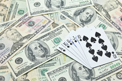 Playing cards on pile of US dollar banknotes Royalty Free Stock Photography