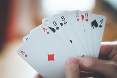 Playing cards: Poker cards in the hand of a young man. Young man is playing cards, cutout of his hands poker gambling leisure concept casino game winning chance royalty free stock image