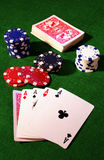 Playing cards and poker chips. A view of playing cards and red, blue and white poker chips on a green felt background.  All four aces are face up at the bottom Royalty Free Stock Photo