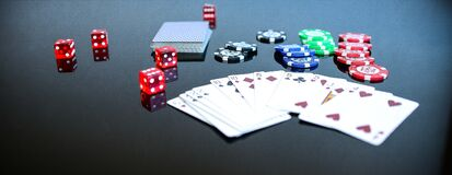 Playing Cards Beside Poker Chips and Dice Royalty Free Stock Images