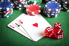 Playing cards, poker chips, and dices on green table Stock Photos