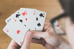 Playing cards: Poker cards in the hand of a man. Man is playing cards, cutout of his hands poker gambling leisure concept casino game winning chance success stock images
