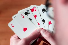 Playing cards: Poker cards in the hand of a man. Man is playing cards, cutout of his hands poker gambling leisure concept casino game winning chance success royalty free stock image