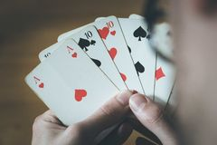 Playing cards: Poker cards in the hand of a man. Man is playing cards, cutout of his hands poker gambling leisure concept casino game winning chance success stock photos