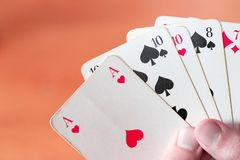 Playing cards: Poker cards in the hand of a man. Man is playing cards, cutout of his hands poker gambling leisure concept casino game winning chance success royalty free stock photo