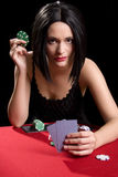 Playing cards red. Determined attractive brunette playing cards at a red poker table Stock Image