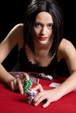 Playing cards red. Determined attractive brunette playing cards at a red poker table Royalty Free Stock Photos