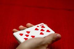 Playing cards. Red background, holding cards in hand Royalty Free Stock Photography