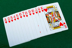 Playing cards red deck on the green background Stock Image