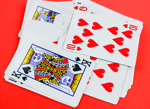 Playing cards on red table Stock Images