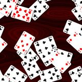 Playing cards scattered on mahogany wooden table - seamless pattern texture background Royalty Free Stock Images