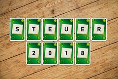 Playing cards with text `Steuer 2018` on a wooden floor stock photo