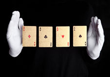 Playing cards trick with ace hands with gloves. On black background Stock Photo