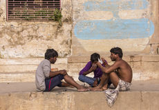 Playing cards in Varanasi. Three young men playing a game of cards on the holy ghats of Varanasi Royalty Free Stock Image