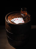 Playing cards and wine glass of cognac on barrel Royalty Free Stock Photo