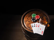Playing cards and wine glass of cognac on barrel.  stock photography