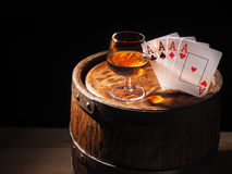 Playing cards and wine glass of cognac on barrel.  royalty free stock images