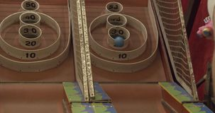 Playing carnival skee ball at a fair. Shot in 4K RAW on a cinema camera stock video footage
