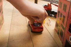 Playing with cars. A closeup of a young child's hand, pushing a red toy car through miniature streets with buildings on the floor Stock Photo