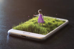 Playing on a cell phone. A little girl chases butterflies on top of a cell phone stock photo
