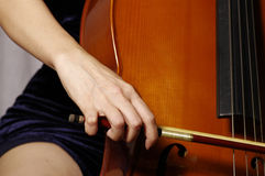 Playing cello. Close up of woman hand playing cello Royalty Free Stock Image