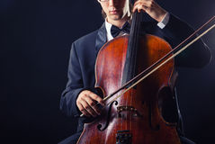 Playing the cello. Cellist playing classical music on cello on black background royalty free stock photography