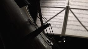 Close up playing the cello. Side view. Playing the cello close up bow strings. Side view stock footage