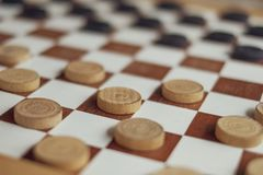 Playing checkers with wooden black and white pawns royalty free stock image