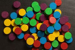 Playing checks on black background. Round, wooden, multicolored, game chips on a black textured background Stock Images