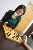 Playing chess. Young white caucasian woman plays chess. Game takes place at home at brown table stock photography