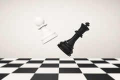 Playing chess concept. Pawn with Queen fighting Royalty Free Stock Image