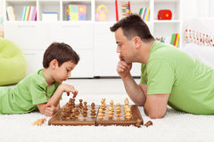 Playing chess with dad. Young boy and his father at home stock image