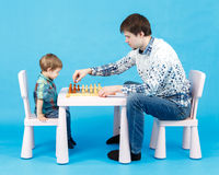 Playing chess with dad - little boy and his father on blue Royalty Free Stock Images
