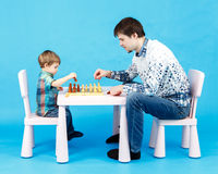Playing chess with dad - little boy and his father on blue Stock Image