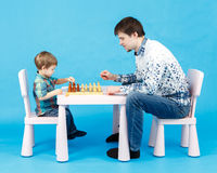Playing chess with dad - little boy and his father on blue Stock Images