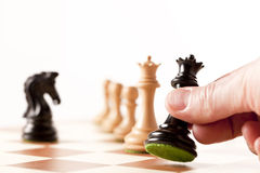 Playing chess - a hand moving black queen on a chessboard Royalty Free Stock Photo