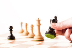 Playing chess - a hand moving black rook on a chessboard Royalty Free Stock Photo