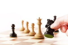 Playing chess - a hand moving chess pieces on a chessboard Royalty Free Stock Images