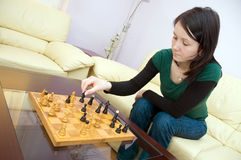 Playing chess at home. Young white caucasian woman plays chess. Game takes place at home at brown table. Player sits on yellow sofa and moves a pawn stock images