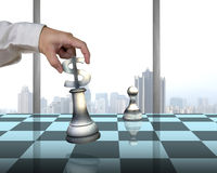 Playing chess with usd symbol piece, pawn and city view. Hand allocating USD 3D symbol piece on chessboard with pawn and city view outside Royalty Free Stock Image