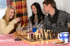 Playing chess winter chalet friends laughing Royalty Free Stock Photography