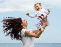 Playing with child. Joyful female playing with adorable infant on fresh air at summer Royalty Free Stock Images